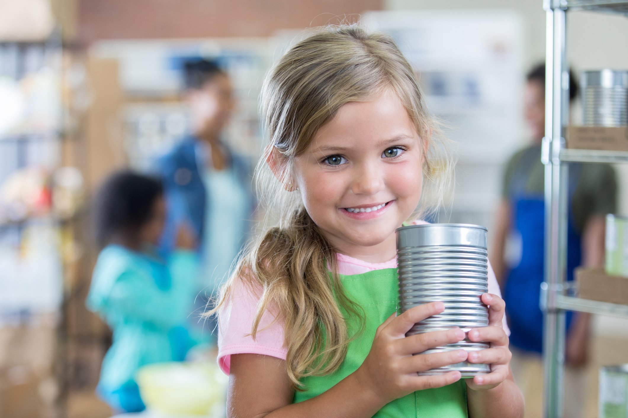 Beautiful little girl holds a can of food while volunteering with her family at at food bank. She is wearing a green apron.