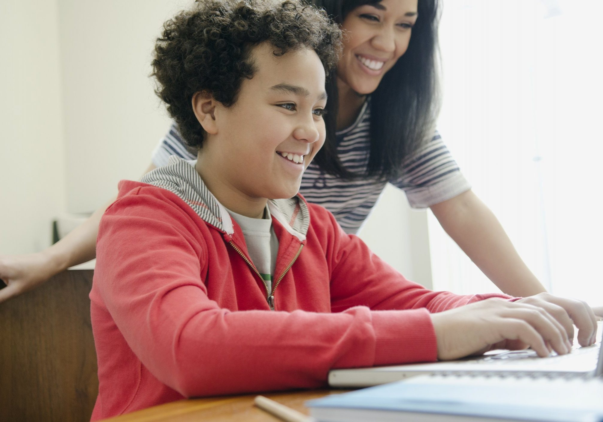 teenager on laptop getting help from mom