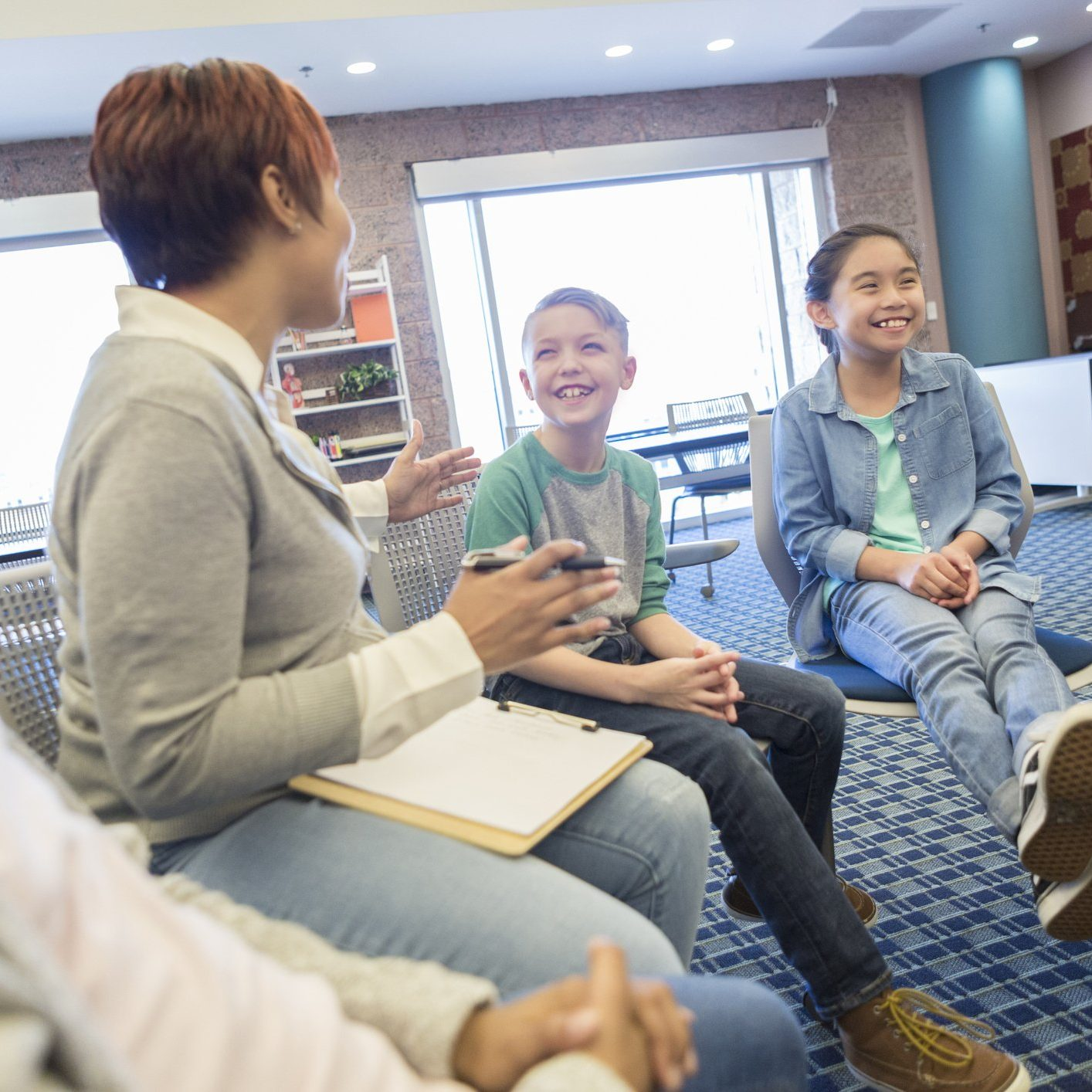 Confident mid adult teacher or school counselor talks with a group of male and female students.